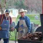 Local volunteers barbeque rib-eye steaks for dinner.