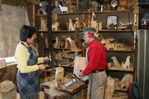 Frances Conklin consults Dennis Sullivan about a carved dog in their Dog Bark Park shop.