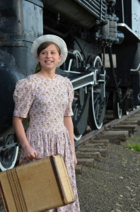 """Chloe Mitchem, 14, poses next to a train. Chloe and her sister Emma play the duel role of Pollyanna in APOD Theatre Productions' musical """"Pollyanna."""""""