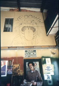 Mark Solomon stands with R. Crumb's mural in his blacksmith shop, Idaho Forge and Fabrication in May 1990, prior to selling his shop and devoting himself full-time to the Latah County Commissioner election. He was elected and later recalled. The R. Crumb mural had been moved to Boise but is now back for Moscow Artwalk. It will be on display at City Hall's Third Street Gallery.