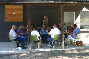 Members of the District Nine Idaho Old Time Fiddlers group sit around in a circle during a campout.