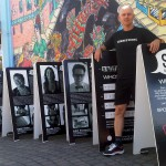 """Marshall Peterson of Spokane stands outside Thomas Hammer Coffee Roasters in Pullman with his outdoor photo exhibit """"S10: The First Wave"""" on display through Saturday. (Photo by Joan Howard)"""