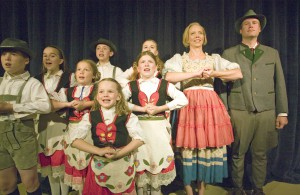 "Todd Payne as Capt. George Von Trapp, right, and Katie McDougall as Maria Rainer, second from right, sing with the Von Trapp children in a scene from the Regional Theatre of the Palouse's production of ""The Sound of Music."""