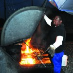 John (Smitty) Smith closes the lid as flames begin to rise during one of his late night barbecue cooking sessions at Smitty's in East Lewiston.