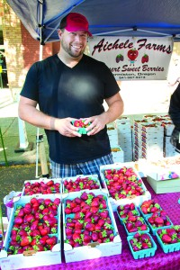 Alison Meyer's photo depicts a vendor of Aichele Farms, who is holding strawberries.