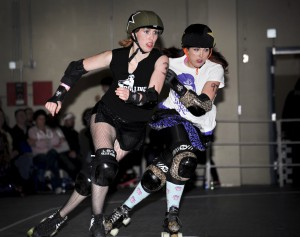 """Kelly """"Kraken the Whip"""" Stewart races a Lilac City jammer during an April 14, 2012, bout at the Spokane County Fairgrounds."""