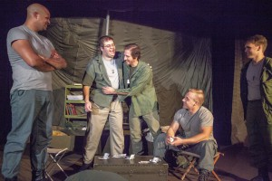 """Capt. John """"Trapper John"""" McIntyre, center left, played by Christopher Burns, and Capt. Benjamin Franklin """"Hawkeye"""" Pierce embrace while watched by Capt. John """"Ugly"""" Black, left, played by Brandon Dudley, Capt. Augustus Bedford """"Duke"""" Forrest, far right, played by Jonathan Shumate, and Capt. Walter """"Walt"""" Waldowski, played by Michael Baszler, during rehearsal for the Pullman Civic Theater production of M*A*S*H on Thursday at the Nye Street Theatre in Pullman."""
