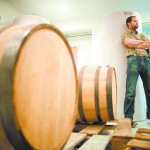 Trent Maier stands besides whiskey barrels full of aging cider at the Whiskey Barrel Cider Company in Pullman, Wash.