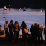 A crowd lines Prospect Avenue to watch the lighted boat parade make it's way along the Snake River.
