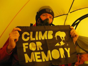 """Nelson Dellis holds a """"Climb for Memory"""" flag inside his tent during a climb. The film, """"Ace of Diamonds,"""" follows Dellis during the World Memory Championships and his climb up Mt. Everest, as an attempt to raise awareness for his """"Climb For Memory"""" foundation, which raises money for Alzheimer's research."""