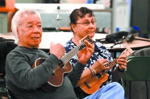 Bill Kaaihue and Margaret Guzman strum their ukuleles.