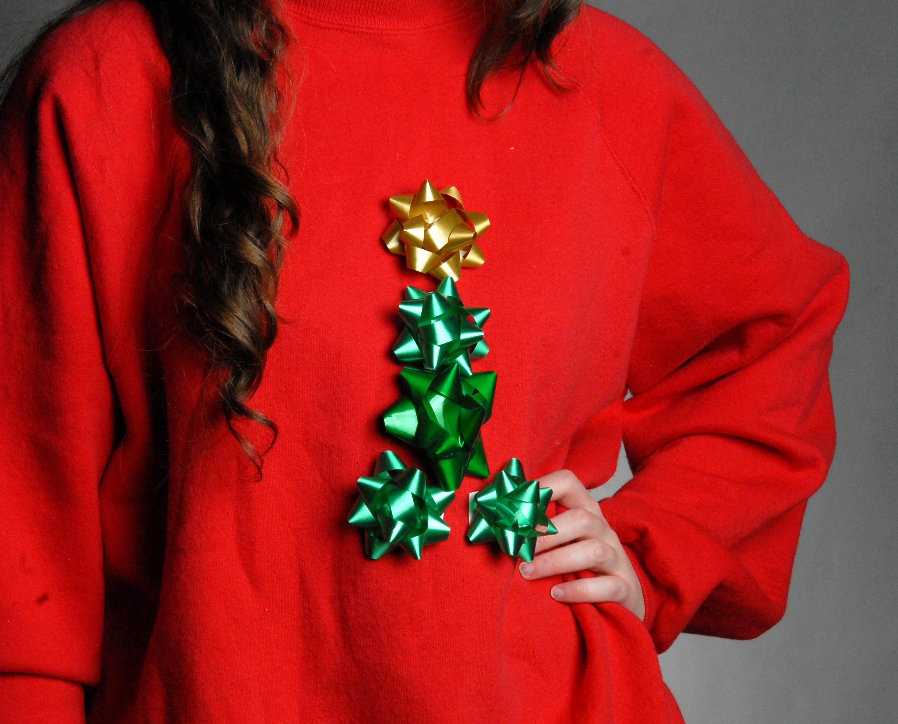 this simple creation can be decorated by covering a sweater an entirely with gift wrapping bows