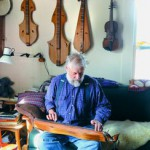 Elwood plays one of his dulcimers which adorn the walls of his home.