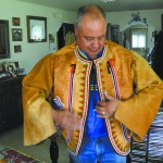 Roger Amerman of Stites tries on the beaded buckskin jacket he is creating for a museum exhibit.