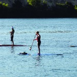 Paddle boarders ply the Snake River in the Lewiston-Clarkston Valley one July evening.