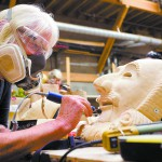 Stephanie Miller works on one of the masks which were hand carved out of basswood for the production.