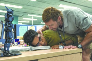 """Deon (Dev Patel) is threatened by Vincent (Hugh Jackman) in """"Chappie."""""""