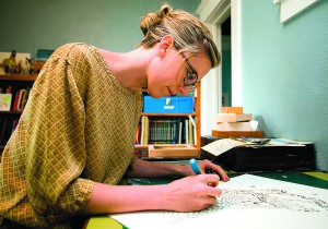 Moscow artist Lauren McCleary demonstrates how she makes a cut-paper piece at her home in Moscow on Wednesday.
