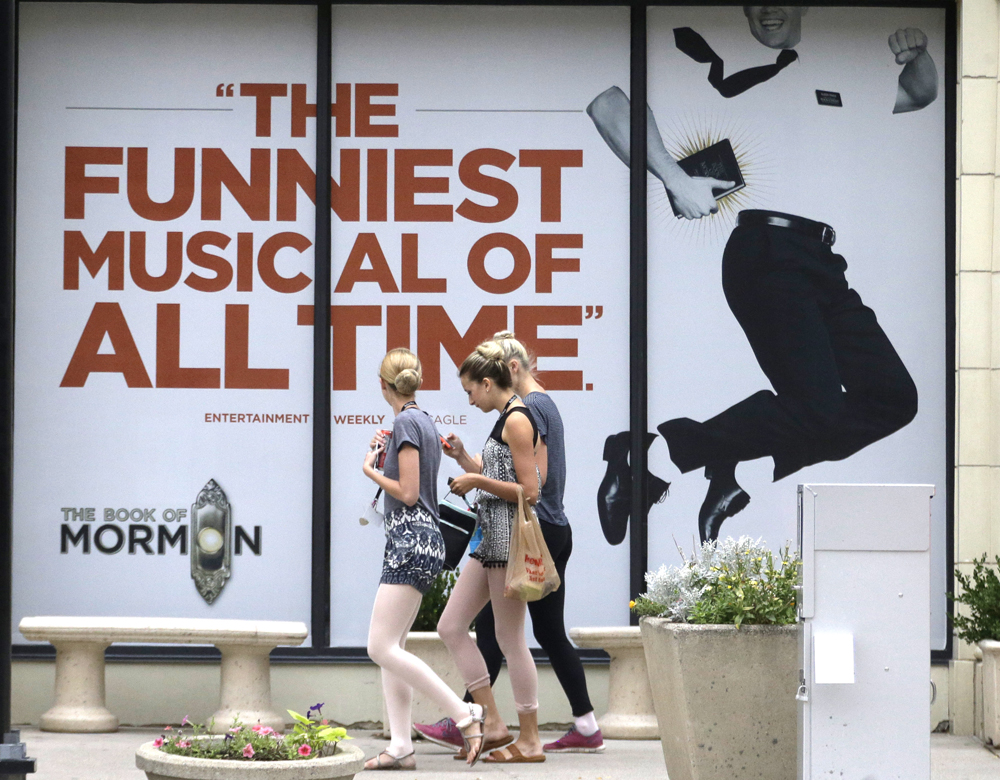 "People walk past signs announcing the ""Book of Mormon"" musical at the Capitol Theatre, Monday, July 27, 2015, in Salt Lake City. The biting satirical musical that mocks Mormons is finally coming to the heart of Mormonlandia, starting a sold-out, two week run on Tuesday, July 28, 2015, at a theater two blocks from the church's flagship temple and headquarters. (AP Photo/Rick Bowmer)"