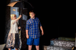 "Bryson Armstrong, playing the lead role of Milo (right), takes shelter under the umbrella of the ""Wetherman,"" played by Andy Cornwall, Tuesday, June 30, during a dress rehearsal for The Phantom Tollbooth in the Pullman Civic Theatre. Nathan Howard/Inland 360"