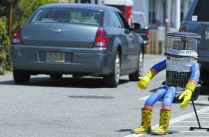 In this July 17 photo a car drives by HitchBOT, a hitchhiking robot in Marblehead, Mass.