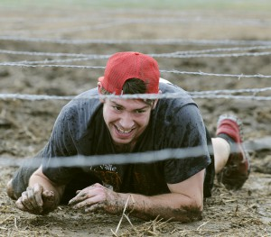 A runner makes his way through the barbed wire crawl at the 2014 LC Valley Down and Dirty Mud Run .
