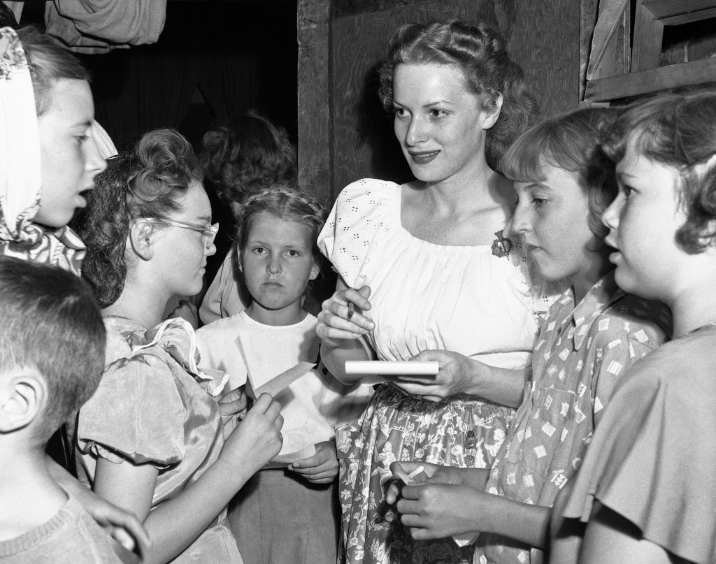 "FILE - This Oct. 27,1950 file photo shows Maureen O'Hara signs autographs for school children of Moab, Utah, while on location there for a new film.  O'Hara,who appeared in such classic films as ""The Quiet Man"