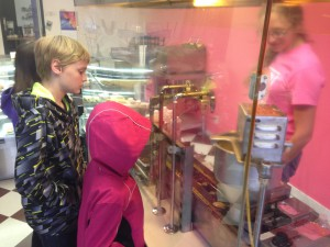 Isaiah and Karah watch doughnuts being made at Buy the Dozen in Moscow