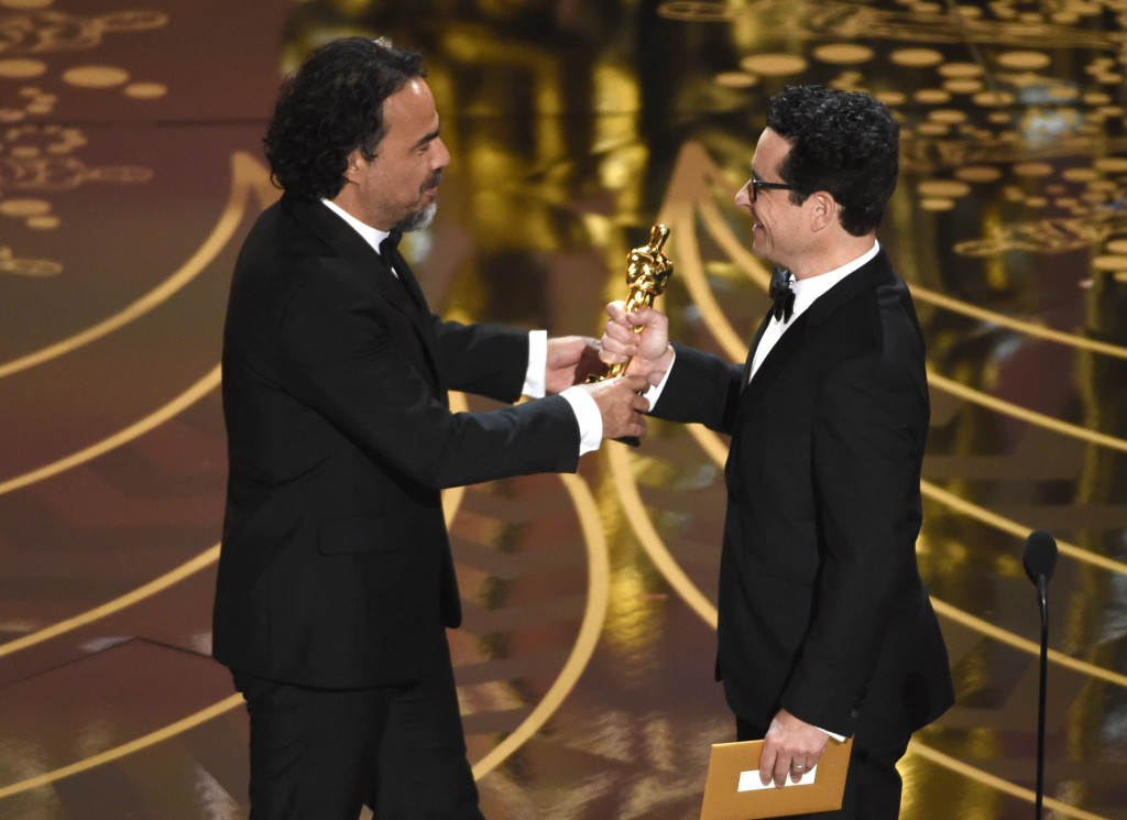 """J.J. Abrams, right, presents Alejandro G. Inarritu with the award for best director for """"The Revenant"""" at the Oscars on Sunday, at the Dolby Theatre in Los Angeles. (Photo by Chris Pizzello/Invision/AP)"""