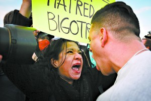 A protester confronts a supporter of Republican presidential candidate Donald Trump in downtown Salt Lake City as Donald Trump gave his first campaign speech in Utah on Friday, Mar. 18, 2016. (Benjamin Zack/Standard-Examiner via AP) LOCAL TELEVISION OUT; MANDATORY CREDIT