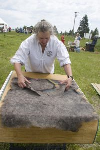 A volunteer demonstrates making felt from wool.