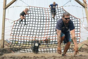 Competitors climb the waterfall cargo net obstacle at the 2015 LC Valley Down and Dirty course.