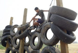 A teen climbs the Tire Wall at the 2015 event.