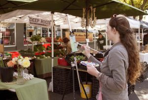 Victoria Lock paints a scene at the Moscow Farmers Market Saturday, Sept. 24 while taking part in the Palouse Plein Air competition.