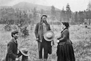 Nez Perce Chief Joseph meets Alice C. Fletcher near Lapwai in 1899. She was the allotting agent sent from Washington, D.C., to administer the congressional act that divided the Nez Perce land into plots. Interpreter James Stuart kneels at left.