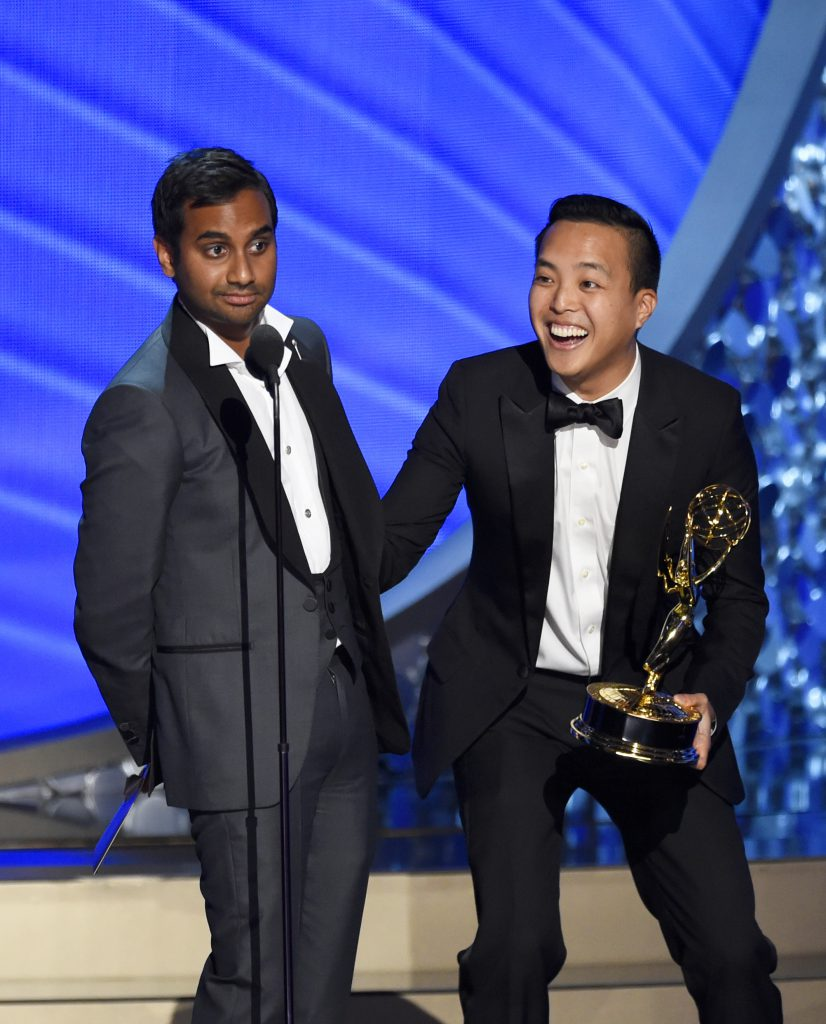 "Aziz Ansari, left, and Kelvin Yu accept the award for outstanding writing for a comedy series for ""Master of None"" at the 68th Primetime Emmy Awards on Sunday, Sept. 18, 2016, at the Microsoft Theater in Los Angeles. (Photo by Chris Pizzello/Invision/AP)"