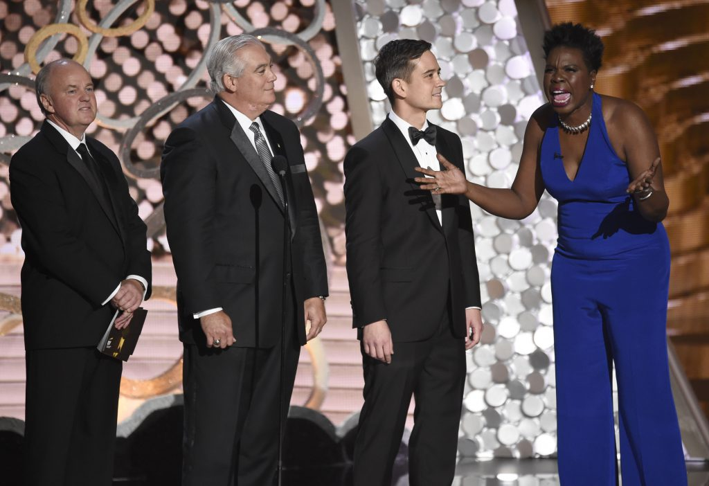 Representatives of Ernst & Young appear on stage with Leslie Jones, right, at the 68th Primetime Emmy Awards on Sunday, Sept. 18, 2016, at the Microsoft Theater in Los Angeles. (Photo by Chris Pizzello/Invision/AP)
