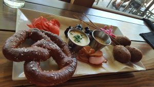 The Appetizer Flight includes a sourdough pretzel, home-made pickles, Brew dogs and bacon wrapped dates.